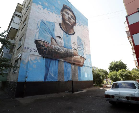 Local residents walk in front of a mural of Argentina player Lionel Messi by Russian street artist Sergey Erofeev pictured on a apartment house wall nearby the Argentina's base camp in Bronnitsy outside Moscow, Russia 19 June 2018.  EPA/Maxim Shipenkov