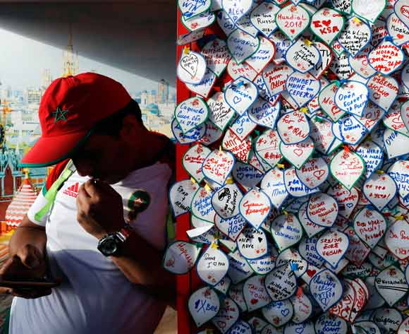 A Tunisian fan checks his mobile next to a wall full of notes written by football fans in the FIFA  World Cup 2018 fan zone in Moscow, Russia, 20 June 2018. Tunisia will face in the FIFA World Cup 2018 on 23 June 2018 in Moscow.  EPA/Felipe Trueba