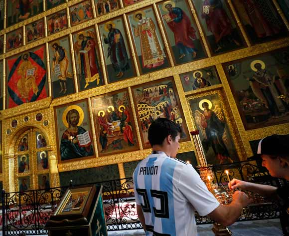 Football fans with Argentinian shirts light a candle in a ultraorthodox church inside the Kazan Kremlin, in Kazan, Russia, 30 June 2018. Argentina faces France in the Round of 16 match of the FIFA World Cup 2018 in Russia. EPA/Felipe Trueba