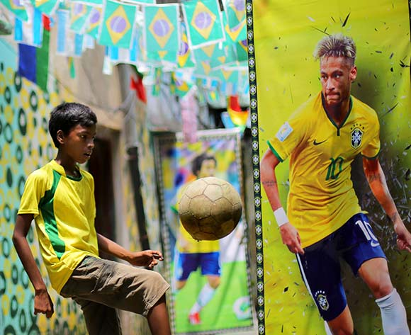 A soccer fan shows his juggle skills next to a poster of Brazil's Neymar in a lane decorated with Brazilian flags and painted walls at the Sonagachi district in Kolkata, eastern India 02 July 2018. The FIFA World Cup 2018 takes place in Russia from 14 June until 15 July 2018. EPA/Piyal Adhikary