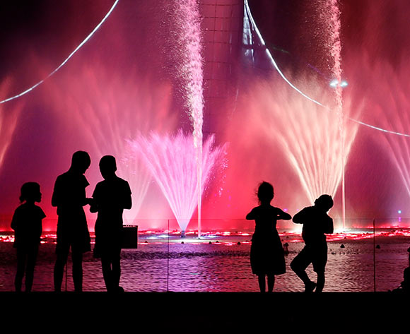 Visitors enjoy a view of a illuminated water fountain at the 2014 Olympic Cauldron with music at the Olympic Park in Adler Sochi, Russia, 02 July 2018. The Fisht Stadium Stadium will host six FIFA World Cup 2018 matches, including one quarter final. The FIFA World Cup will take place in Russia from 14 June to 15 July 2018. EPA/Ronald Wittek