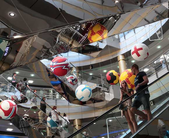 A couple descends an escalator next to giant soccer balls suspended from the ceiling of a shopping mall in Kazan, Russia, 04 July 2018. Brazil will face Belgium in their FIFA World Cup 2018 quarter final soccer match in Kazan on 06 July 2018. EPA/Wallace Woon
