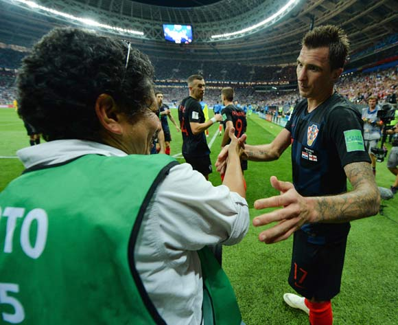 Mario Mandzukic (R) of Croatia helps up photographer Yuri Cortez after he was knocked off his seat during the Croatian players 'celebration of Mandzukic's winning goal in the FIFA World Cup 2018 semi final soccer match between Croatia and England in Moscow, Russia, 11 July 2018. Croatia won 2-1. EPA/Peter Powell